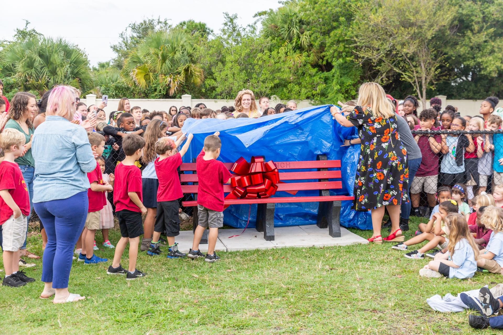 students and staff unveiling bench