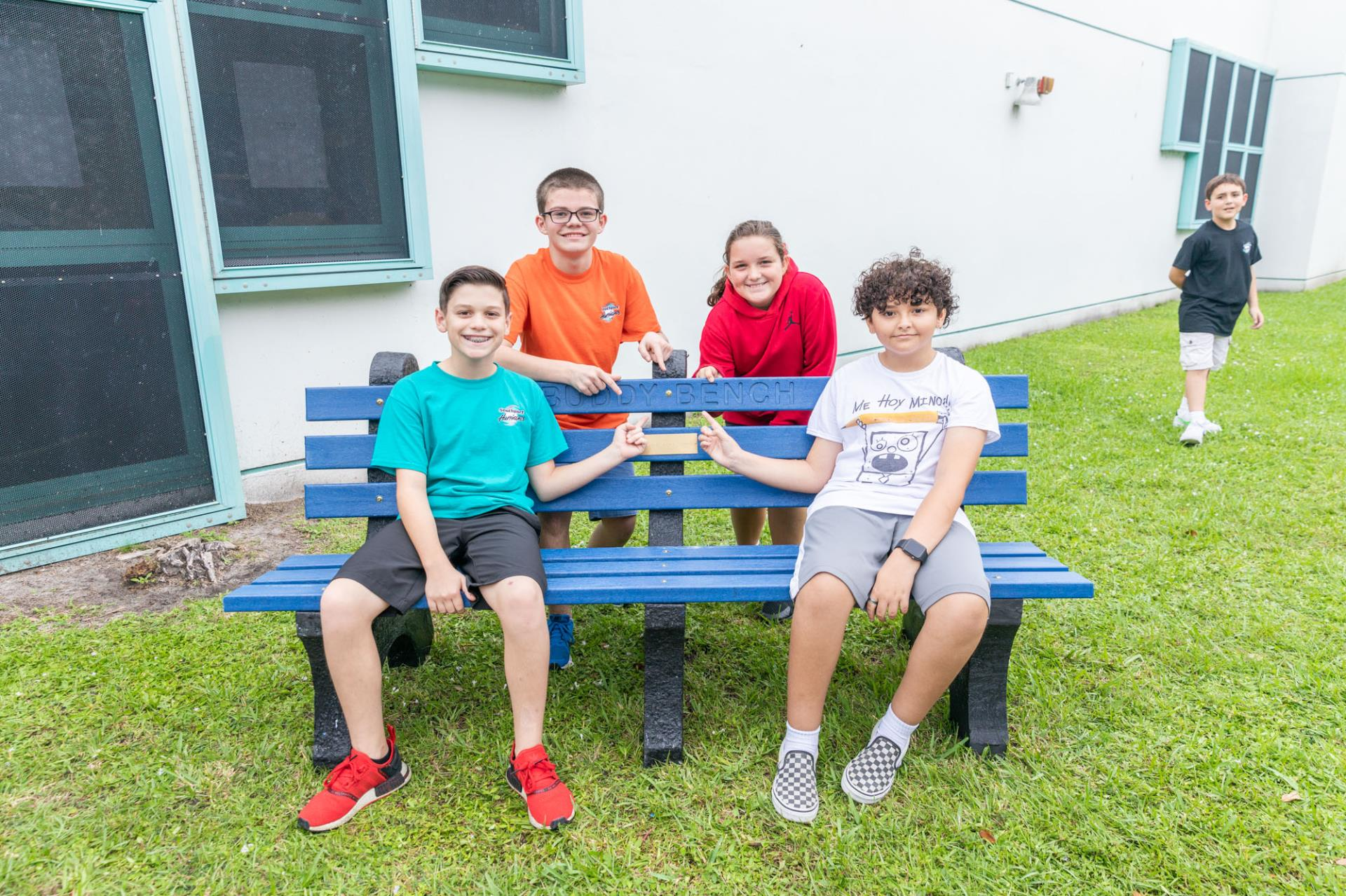 students smiling and sitting on bench
