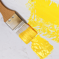 paintbrush on white wall with yellow paint