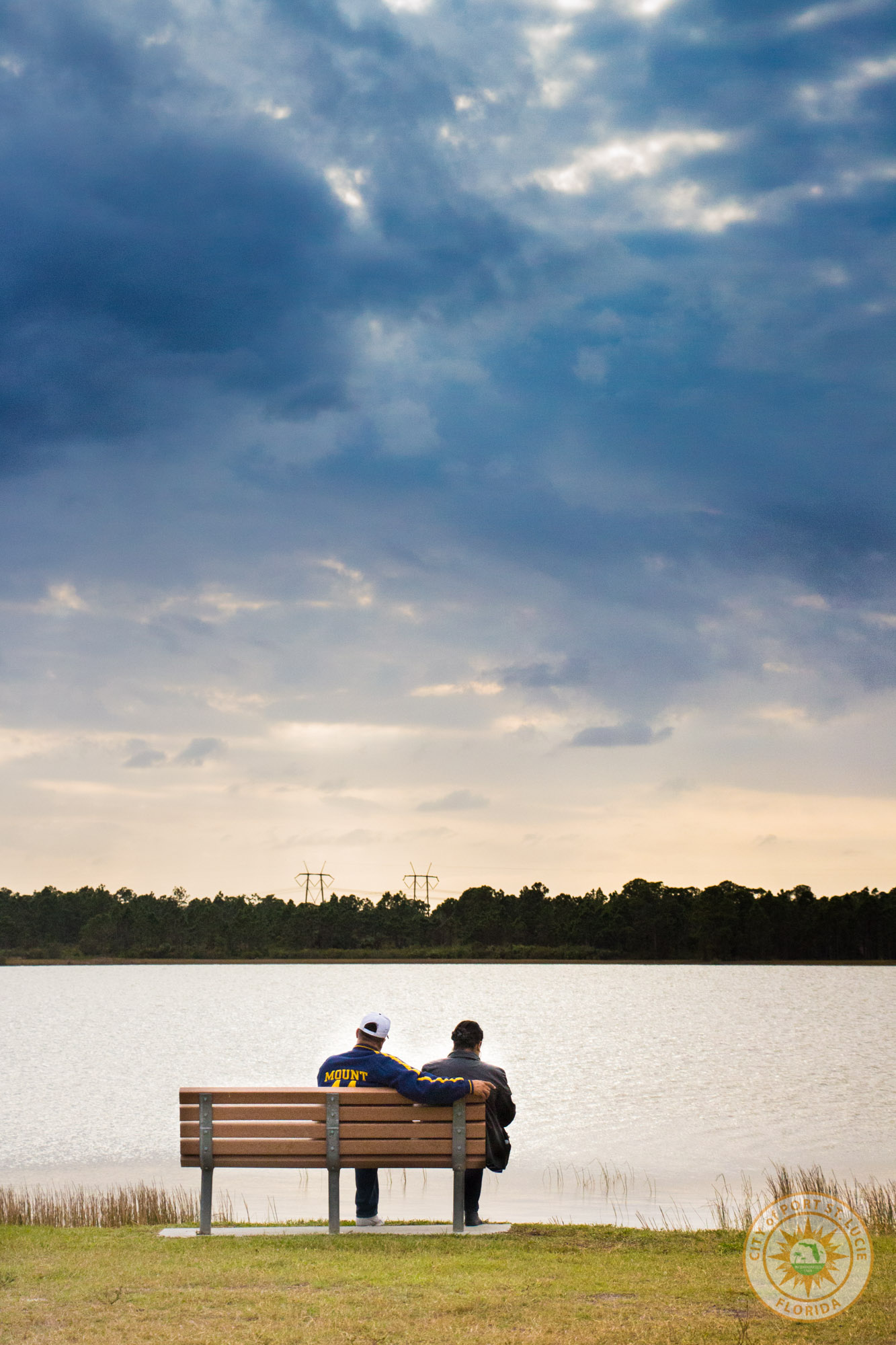 Couple sitting on bench enjoying the relaxing lake