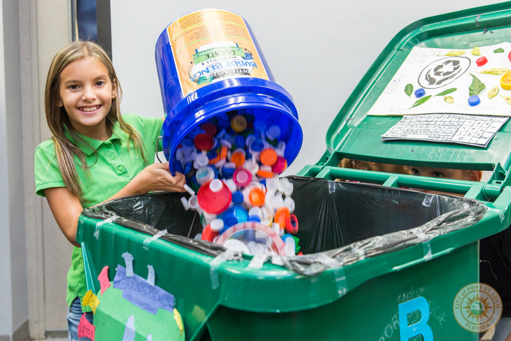Student adding bucket of caps into recycling bin